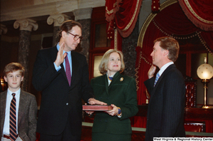 "[""Senator John D. (Jay) Rockefeller places his left hand on a bible and raises his right hand to take the oath of office for his second term as Senator from West Virginia.""]%"