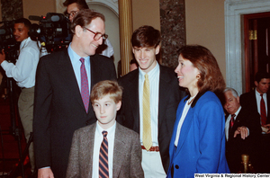 "[""Senator John D. (Jay) Rockefeller stands with two of his sons and talks with an unidentified woman after his second Senate Swearing-In Ceremony.""]%"