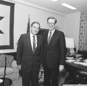 "[""Senator John D. (Jay) Rockefeller stands with an unidentified man for a photograph in his office.""]%"