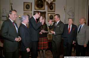 "[""This photo shows Vice President George H. W. Bush administering the oath of office to Senator John D. (Jay) Rockefeller. The Senator's wife, Sharon Rockefeller, holds the Bible.""]%"