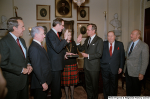 "[""Senator John D. (Jay) Rockefeller is sworn into office by Vice President George H. W. Bush, surrounded by Senate colleagues and his wife Sharon Rockefeller.""]%"