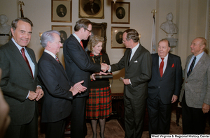 "[""Senator John D. (Jay) Rockefeller shakes hands with Vice President George H. W. Bush after taking the oath at Senate Swearing-In Ceremony.""]%"