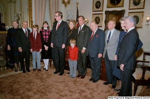 "[""Family, fellow Senators, and Vice President George H. W. Bush surround Senator John D. (Jay) Rockefeller after the Senate swearing-in ceremony. (Wide angle photograph)""]%"