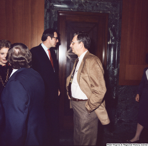 "[""Senator John D. (Jay) Rockefeller speak with unidentified individuals following the Senate Swearing-In Ceremony.""]%"