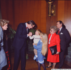 "[""Senator John D. (Jay) Rockefeller greets a smiling young supporter following his Senate Swearing-In Ceremony.""]%"