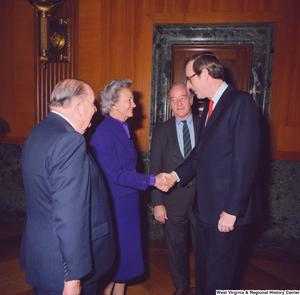 "[""Former Senator Jennings Randolph and Senator John D. (Jay) Rockefeller speak with two unidentified supporters at the Senate Swearing-In Ceremony.""]%"