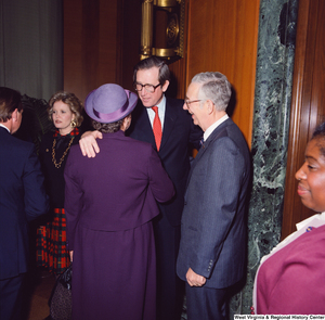 "[""Senator John D. (Jay) Rockefeller embraces an unidentified woman in a purple dress after he has been sworn into office.""]%"