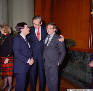"[""Senator John D. (Jay) Rockefeller embraces two unidentified supporters after being sworn into office.""]%"