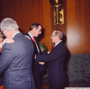 "[""An unidentified supporter shakes hands with Senator John D. (Jay) Rockefeller at the Senate Swearing-In Ceremony.""]%"
