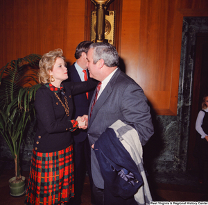 "[""Sharon Rockefeller shakes the hand of a supporter at the Senate Swearing-In Ceremony. Senator John D. (Jay) Rockefeller can be partially seen in the background.""]%"