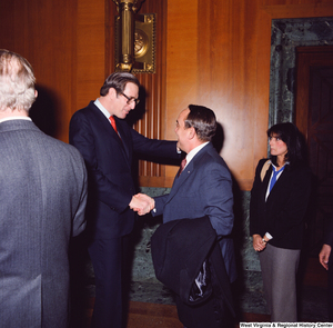 "[""An unidentified supporter and Senator John D. (Jay) Rockefeller shake hands following the Senate Swearing-In Ceremony.""]%"