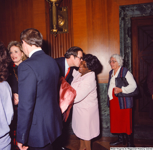 "[""Senator John D. (Jay) Rockefeller kisses the cheek of an unidentified supporter at the Senate Swearing-In Ceremony. Sharon Rockefeller can be partially seen to the left.""]%"