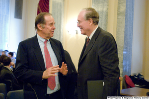 "[""Senator John D. (Jay) Rockefeller talks with an unidentified man before a Commerce Committee hearing.""]%"