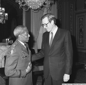 "[""Senator John D. (Jay) Rockefeller speaks with Major General Ernest Harrell in one of the Senate buildings.""]%"
