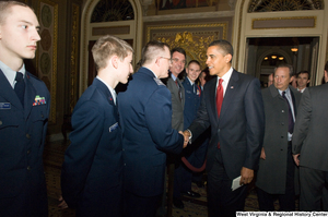 "[""President Barack Obama shakes hands with a member of the Air Force during a visit to the U.S. Capitol Building.""]%"