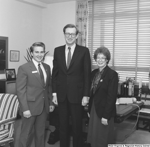"[""Senator John D. (Jay) Rockefeller stands with two unidentified individuals in his office. The boy in the left part of the photograph has a name badge on that says \""Thomas Lucas\"", but the rest of the text is indistinguishable and it is not known what kind of group he is representing.""]%"