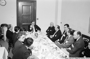 "[""Senator John D. (Jay) Rockefeller sits at the head of a table during a breakfast event with numerous unidentified individuals.""]%"