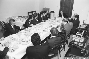 "[""Senator John D. (Jay) Rockefeller sits at the head of the table during a breakfast banquet in the Senate.""]%"