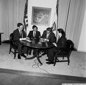 "[""Senator John D. (Jay) Rockefeller opens up a report as he sits around a table with Congressman Nick Rahall and two representatives of China Steel and the Island Creek Coal Company.""]%"