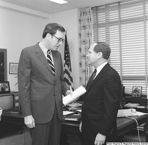 "[""With a rolled piece of paper in his hand, Senator John D. (Jay) Rockefeller speaks to an unidentified individual in his office.""]%"