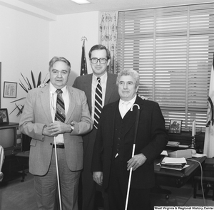 "[""Two men from the West Virginia Chapter of the National Federation of the Blind pose for a photograph with Senator John D. (Jay) Rockefeller in his Washington office.""]%"
