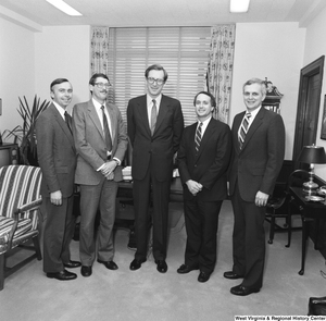 "[""Senator John D. (Jay) Rockefeller stands in the middle of a group of four unidentified individuals in his office.""]%"
