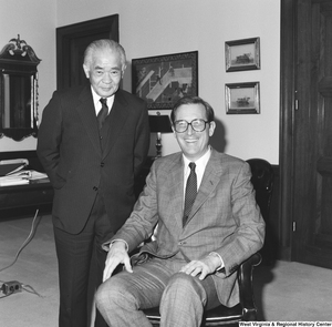 "[""An unidentified individual stands beside Senator John D. (Jay) Rockefeller as he sits in a chair.""]%"