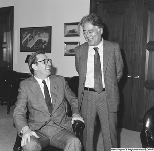 "[""Senator John D. (Jay) Rockefeller sits in a chair and laughs with the unidentified man standing next to him.""]%"