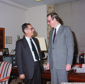 "[""This color photograph shows Senator John D. (Jay) Rockefeller speaking with an unidentified individual in his office.""]%"