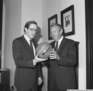 "[""Senator John D. (Jay) Rockefeller holds a basketball with an unidentified man in his office.""]%"