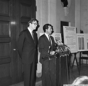 "[""Senator John D. (Jay) Rockefeller stands next to Senator H. John Heinz III as he speaks at a press event in support of their piece of legislation, the Dislocated Workers Improvement Act of 1987.""]%"
