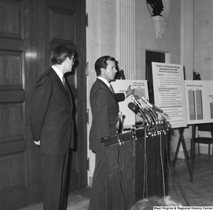 "[""Senator John D. (Jay) Rockefeller stands next to Senator H. John Heinz III as he discusses the Dislocated Workers Improvement Act of 1987 at a press event.""]%"