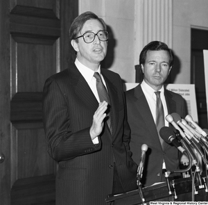 "[""Senator H. John Heinz III stands behind Senator John D. (Jay) Rockefeller as he speaks at a press event supporting the Dislocated Workers Improvement Act of 1987.""]%"