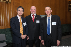 "[""Three men stand together at a Washington corporate event.""]%"