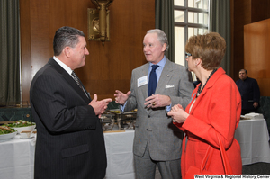 "[""A man talks with two other people at a Welcome to Washington luncheon.""]%"