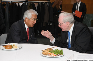 "[""Senator John D. (Jay) Rockefeller speaks with an industry leader during a Welcome to Washington luncheon.""]%"