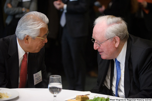 "[""Senator John D. (Jay) Rockefeller sits beside a representative of the Toyota Motor Corporation at a luncheon event in Washington.""]%"