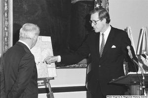 "[""Senator John D. (Jay) Rockefeller pointing to a map of West Virginia during a press event.""]%"