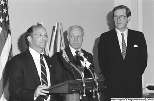 "[""Senator John D. (Jay) Rockefeller stands next to two unidentified men at a press event.""]%"