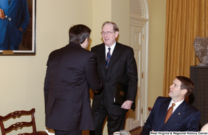 "[""Senator John D. (Jay) Rockefeller shakes hands with an unidentified man at a lunch event at the Senate.""]%"