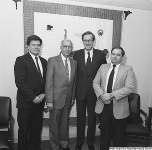 "[""Senator John D. (Jay) Rockefeller stands with three unidentified men in his office.""]%"