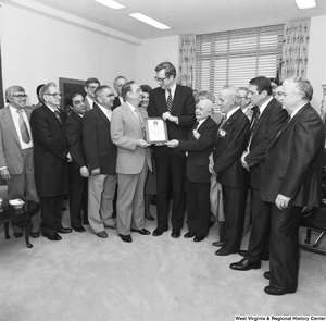 "[""Surrounded by a large group in his office, Senator John D. (Jay) Rockefeller accepts an award from the Tin Mill Employees Federal Credit Union.""]%"