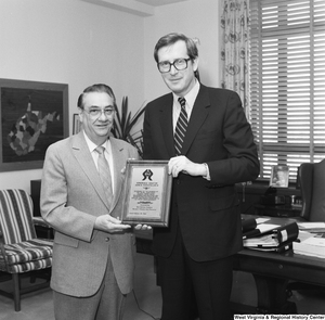 "[""Senator John D. (Jay) Rockefeller holds his award plaque and poses for a photograph with an unidentified representative of the Tin Mill Employees Federal Credit Union.""]%"