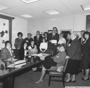 "[""Senator John D. (Jay) Rockefeller holds a plaque with members of a large unidentified group in his office.""]%"