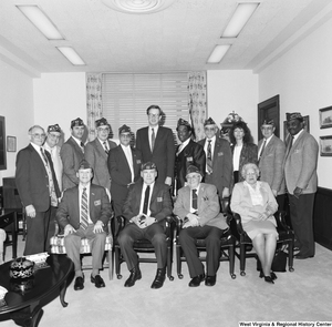 "[""Senator John D. (Jay) Rockefeller stands in the center of a large group of Veterans of Foreign Wars members who are visiting his office.""]%"