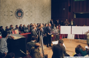 "[""This is a wide angle photograph showing a row of staffers and Senators standing behind Senator John D. (Jay) Rockefeller as he speaks to the media during a press event for the Pepper Commission.""]%"