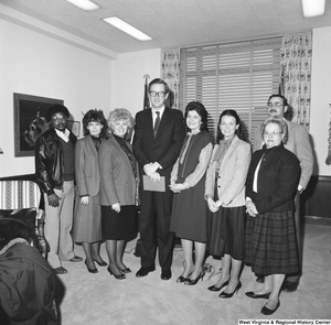 "[""Senator John D. (Jay) Rockefeller holds an envelope and poses for a photograph with representatives from the West Virginia Association of Community Health Centers.""]%"