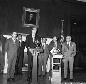 "[""Senator John D. (Jay) Rockefeller speaks behind a podium in one of the Senate buildings during a press conference for the Staggers Rail Reform bill. West Virginia Congressmen Nick Rahall and Bob Wise can be seen standing behind him.""]%"
