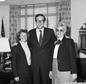 "[""Senator John D. (Jay) Rockefeller stands for a photograph in his office with two unidentified women.""]%"