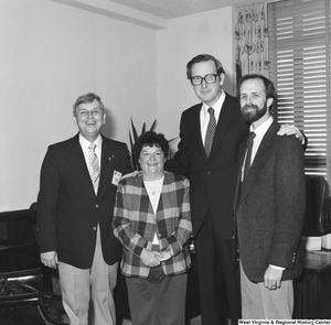 "[""Senator John D. (Jay) Rockefeller poses for a photograph with an unidentified group of three visitors in his Washington office.""]%"